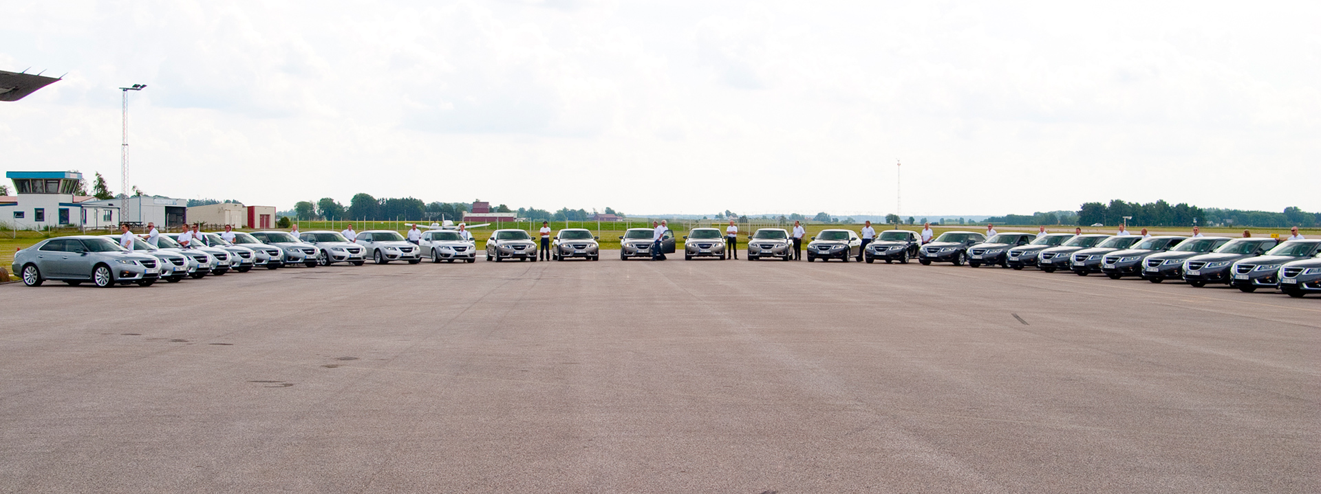 Saab cars lined up at an airfield