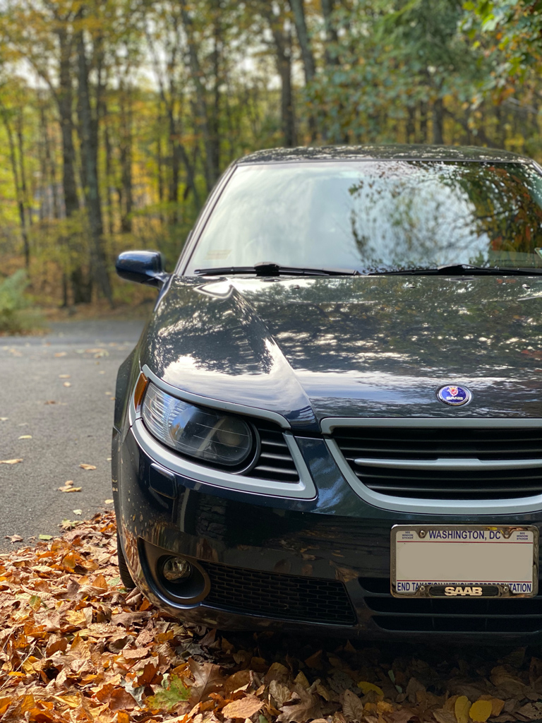 Blue Saab 9-5 on a road with leaves and forest